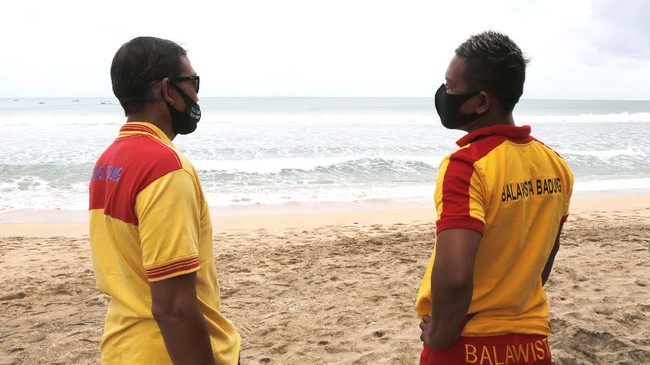 Rescue team wearing face masks stand guard at Kuta beach, Bali, Indonesia on Thursday, July 9, 2020. Indonesia's resort island of Bali reopened after a three-month virus lockdown Thursday, allowing local people and stranded foreign tourists to resume public activities before foreign arrivals resume in September.(AP Photo/Firdia Lisnawati)