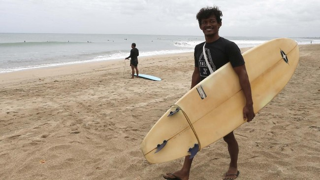 A man carries his surfboard at Kuta beach, Bali, Indonesia on Thursday, July 9, 2020. Indonesia's resort island of Bali reopened after a three-month virus lockdown Thursday, allowing local people and stranded foreign tourists to resume public activities before foreign arrivals resume in September. (AP Photo/Firdia Lisnawati)