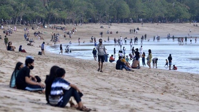 Wisatawan mengunjungi kawasan Pantai Kuta, Badung, Bali, Kamis (9/7/2020). Pengelola Pantai Kuta mulai membuka kembali kawasan yang merupakan salah satu destinasi pariwisata utama di Pulau Dewata tersebut setelah sebelumnya sempat ditutup selama lebih dari tiga bulan sebagai upaya pencegahan penyebaran pandemi COVID-19. ANTARA FOTO/Fikri Yusuf/aww.