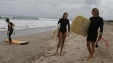 Foreign tourists carry their surf boards at Kuta beach, Bali, Indonesia on Thursday, July 9, 2020. Indonesia's resort island of Bali reopened after a three-month virus lockdown Thursday, allowing local people and stranded foreign tourists to resume public activities before foreign arrivals resume in September. (AP Photo/Firdia Lisnawati)