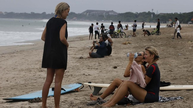 Tourists are seen at Kuta beach, Bali, Indonesia on Thursday, July 9, 2020. Indonesia's resort island of Bali reopened after a three-month virus lockdown Thursday, allowing local people and stranded foreign tourists to resume public activities before foreign arrivals resume in September. (AP Photo/Firdia Lisnawati)