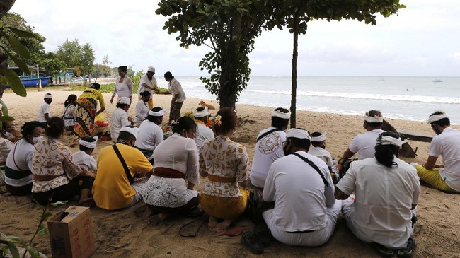 Balinese Hindu gather during a ritual at Kuta beach, Bali, Indonesia on Thursday, July 9, 2020. Indonesia's resort island of Bali reopened after a three-month virus lockdown Thursday, allowing local people and stranded foreign tourists to resume public activities before foreign arrivals resume in September.(AP Photo/Firdia Lisnawati)