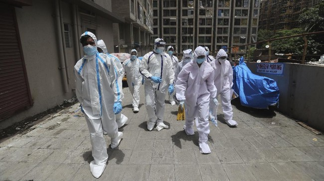 Health workers walks back after conducting a free medical checkup at residential building in Mumbai, India, Thursday, July 2, 2020. Indian Prime Minister Narendra Modi said in a live address Tuesday that the country's coronavirus death rate is under control, but that the country is at a