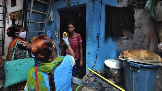 A health worker screens people for COVID-19 symptoms at Dharavi, one of Asia's biggest slums, in Mumbai, India, Monday, July 6, 2020. India has overtaken Russia to become the third worst-affected nation by the coronavirus pandemic. (AP Photo/Rafiq Maqbool)