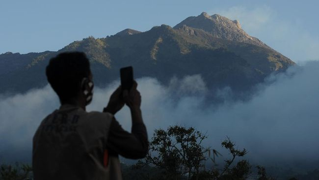Seorang relawan mengabadikan video suasana Gunung Merapi yang terlihat dari kawasan Selo, Boyolali, Jawa Tengah, Rabu (8/7/2020). Bedasarkan data pengamatan Balai Penyelidikan dan Pengembangan Teknologi Kebencanaan Geologi (BPPTKG), pascaerupsi Gunung Merapi pada 21 Juni 2020 terjadi peningkatan deformasi atau perubahan tubuh Gunung Merapi sebesar 0,5 sentimeter per hari. ANTARA FOTO/Aloysius Jarot Nugroho/foc.
