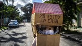 Feridia Rojas, a retired nurse, wears a cardboard box as a protective measure against the spread of the new coronavirus, in Havana, Cuba, Wednesday, July 8, 2020. The 82-year-old pensioner shuffles through the streets of Havana on shopping excursions wearing the cardboard box with a handwritten message that reads in Spanish,