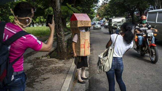 Passersby take photos of Feridia Rojas, a retired nurse, wearing her cardboard box as a protective measure against the spread of the new coronavirus, in Havana, Cuba, Wednesday, July 8, 2020.  The 82-year-old pensioner shuffles through the streets of Havana on shopping excursions wearing the cardboard box, with a handwritten message that reads in Spanish,
