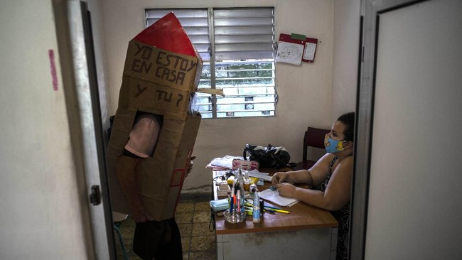 Retired nurse Feridia Rojas wearing a cardboard box as a protective measure against the spread of the new coronavirus, stops in for a friendly visit with the family doctor, in Havana, Cuba, Wednesday, July 8, 2020. The 82-year-old pensioner shuffles through the streets of Havana on shopping excursions wearing the cardboard box, with a handwritten message that reads in Spanish,