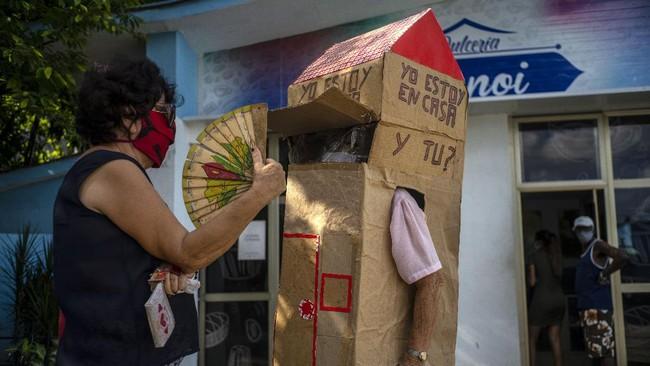 A woman chats with retired nurse Feridia Rojas who wears a cardboard box as a protective measure against the spread of the new coronavirus, in Havana, Cuba, Wednesday, July 8, 2020.  The 82-year-old pensioner shuffles through the streets of Havana on shopping excursions wearing the cardboard box, with a handwritten message that reads in Spanish,