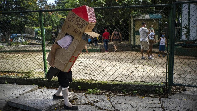 Feridia Rojas, a retired nurse, wears a cardboard box as a protective measure against the spread of the new coronavirus, in Havana, Cuba, Wednesday, July 8, 2020.  The 82-year-old pensioner shuffles through the streets of Havana on shopping excursions wearing the cardboard box, with a handwritten message that reads in Spanish: