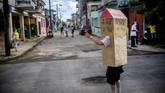Retired nurse Feridia Rojas wears a cardboard box as a protective measure against the spread of the new coronavirus, in Havana, Cuba, Wednesday, July 8, 2020.  The 82-year-old pensioner shuffles through the streets of Havana on shopping excursions wearing the cardboard box, with a handwritten message that reads in Spanish,