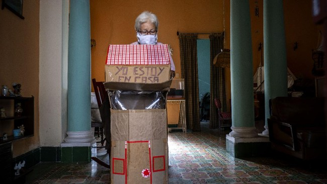 Retired nurse Feridia Rojas prepares to put on her cardboard box she uses as a protective measure against the spread of the new coronavirus, in Havana, Cuba, Wednesday, July 8, 2020.  The 82-year-old pensioner shuffles through the streets of Havana on shopping excursions wearing the cardboard box, with a handwritten message that reads in Spanish,