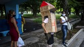 Feridia Rojas, a retired nurse, wears a cardboard box as a protective measure against the spread of the new coronavirus, in Havana, Cuba, Wednesday, July 8, 2020.  The 82-year-old pensioner shuffles through the streets of Havana on shopping excursions wearing the cardboard box, with a handwritten message that reads in Spanish,
