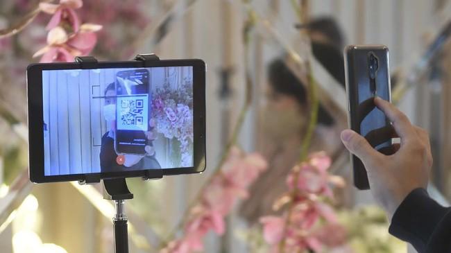 Tamu undangan memindai barcode undangan dalam simulasi pernikahan di era normal baru di Jakarta, Kamis (9/7/2020). Simulasi itu dilakukan dengan protokol COVID-19 yang ketat. ANTARA FOTO/Akbar Nugroho Gumay/nz