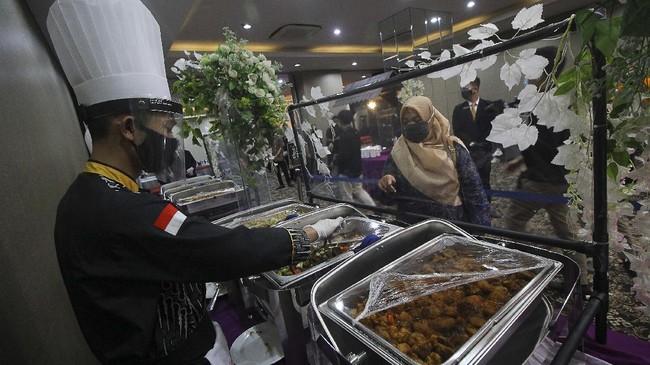 Juru masak mengenakan masker, pelindung wajah dan sarung tangan saat melayani tamu undangan pada simulasi resepsi pernikahan di masa normal baru antara Kumala dan Putri di Hotel Royal Singosari Cendana, Surabaya, Jawa Timur, Senin (6/7/2020). Kegiatan simulasi resepsi pernikahan tersebut bertujuan untuk mengedukasi masyarakat tentang pentingnya penerapan protokol kesehatan dalam acara pernikahan guna mencegah penyebaran dan penularan COVID-19 di masa normal baru. ANTARA FOTO/Moch Asim/wsj.