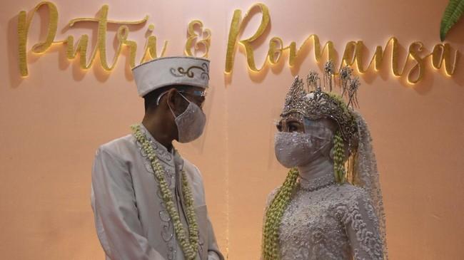 Pasangan pengantin Kumala dan Putri berbincang dengan mengenakan masker dan pelindung wajah saat simulasi resepsi pernikahan di masa normal baru di Hotel Royal Singosari Cendana, Surabaya, Jawa Timur, Senin (6/7/2020). Kegiatan simulasi resepsi pernikahan tersebut bertujuan untuk mengedukasi masyarakat tentang pentingnya penerapan protokol kesehatan dalam acara pernikahan guna mencegah penyebaran dan penularan COVID-19 di masa normal baru. ANTARA FOTO/Moch Asim/wsj.