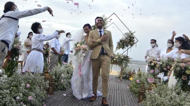 Sejumlah tamu undangan menyambut pasangan pengantin saat simulasi penyelenggaraan kegiatan pernikahan di kawasan Nusa Dua, Badung, Bali, Senin (6/7/2020). Kegiatan simulasi yang diselenggarakan Bali Wedding Association tersebut dilakukan sebagai upaya sosialisasi dan pedoman penyelenggaraan kegiatan pernikahan yang menerapkan protokol kesehatan pencegahan COVID-19 secara ketat selama masa normal baru. ANTARA FOTO/Fikri Yusuf/hp.