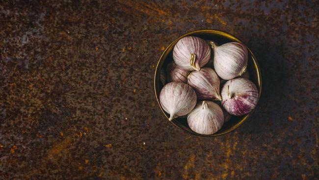 Single clove garlic in a bowl on rusty background