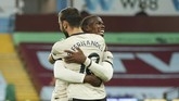 Manchester United's Paul Pogba celebrates with teammate Bruno Fernandes after scoring his team's third goal during the English Premier League soccer match between Aston Villa and Manchester United at Villa Park in Birmingham, England, Thursday, July 9, 2020. (AP PhotoAndrew Boyers,Pool)
