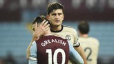 Manchester United's Harry Maguire, right, embraces Aston Villa's Jack Grealish after the English Premier League soccer match between Aston Villa and Manchester United at Villa Park in Birmingham, England, Thursday, July 9, 2020. (AP Photo/Oli Scarff,Pool)