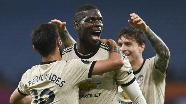 Manchester United's Paul Pogba, centre, celebrates with teammates after scoring his team's third goal during the English Premier League soccer match between Aston Villa and Manchester United at Villa Park in Birmingham, England, Thursday, July 9, 2020. (AP Photo/Shaun Botterill,Pool)