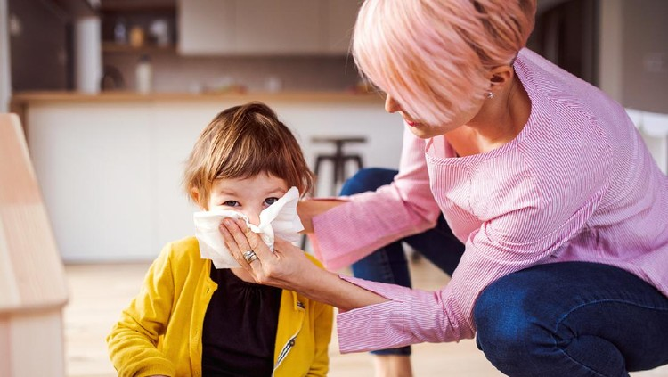 Young mother blowing her small daughter's nose when playing at home.