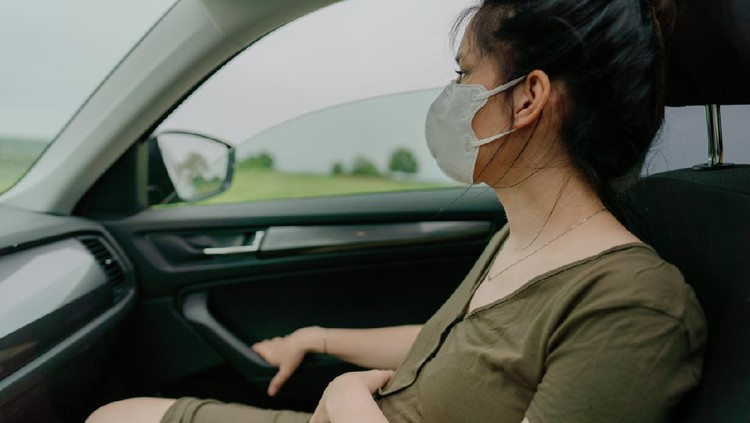 Young pregnant woman behind the steering wheel having contractions