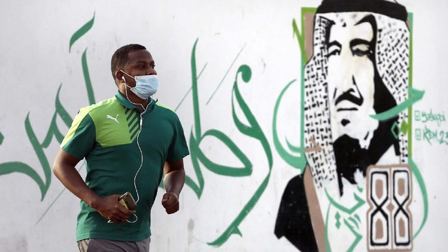 A man wears a face mask to help curb the spread of the coronavirus, as he runs past a graffiti portrait of King Salman, in Jiddah, Saudi Arabia, Sunday, June 28, 2020. The Arabic reads,