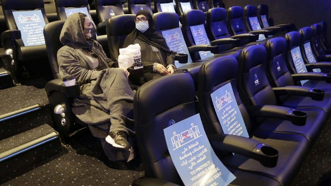 Saudi movie viewers wearing face masks to help curb the spread of the coronavirus, as posters showing the social distancing restrictions are seen at VOX Cinema hall in Jiddah, Saudi Arabia, Friday, June 26, 2020. (AP Photo/Amr Nabil)