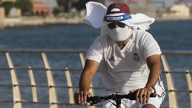 A vacationer rides his bicycle while wearing a face shield and mask to help prevent the spread of the coronavirus, at the Red Sea beach in Jiddah, Saudi Arabia, Thursday, July 9, 2020. (AP Photo/Amr Nabil)