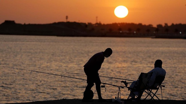 Vacationers fish during sunset at the Red Sea beach, in Jiddah, Saudi Arabia, Thursday, July 9, 2020. (AP Photo/Amr Nabil)