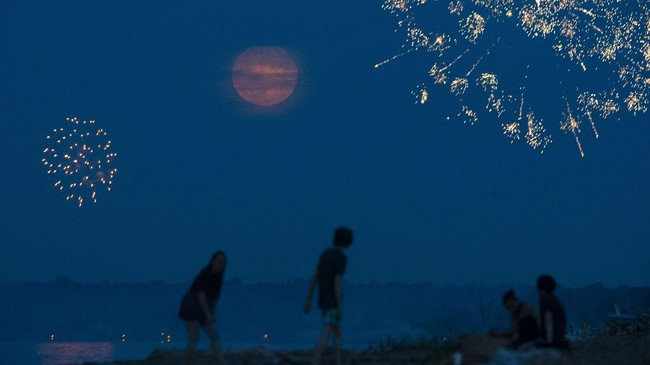 Revelers look out over Wisconsin Point as fireworks were shot off and a waxing gibbous moon rose over the horizon, seen from Superior, Wis., Saturday, July 4, 2020. (Alex Kormann/Star Tribune via AP)