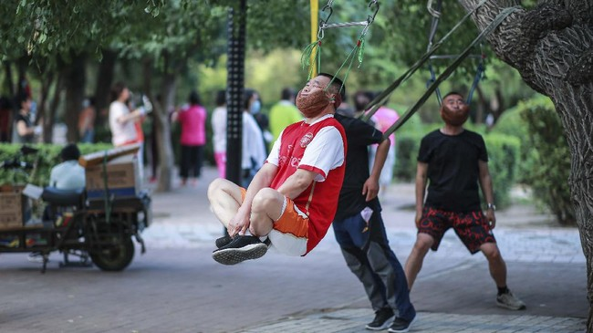 This photo taken on July 5, 2020 shows a man doing exercise as he hangs on a tree in Shenyang in China's northeastern Liaoning province. (Photo by STR / AFP) / China OUT