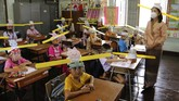 A teacher and students wearing hats designed for space keeper, practice social distancing to help curb the spread of the coronavirus at Ban Pa Muad School in Chiang Mai, north of Thailand, Friday,  July 3, 2020. (AP Photo/ Wichai Taprieu)