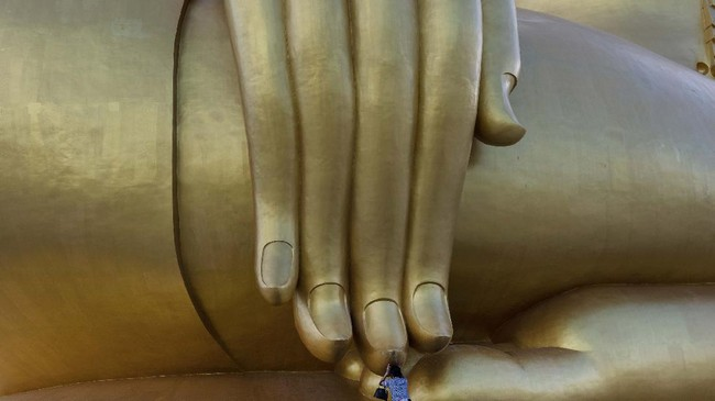 In this photo taken on July 2, 2020, a woman prays under the fingertips of the largest Buddha statue in Thailand, in Ang Thong province, north of Bangkok, as authorities reopened sites to tourists following lockdowns to halt the spread of the COVID-19 novel coronavirus. (Photo by Alex OGLE / AFP)