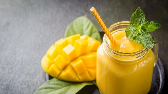 Refreshing and healthy mango smoothie in a glass with fresh fruit over stone background with copy space