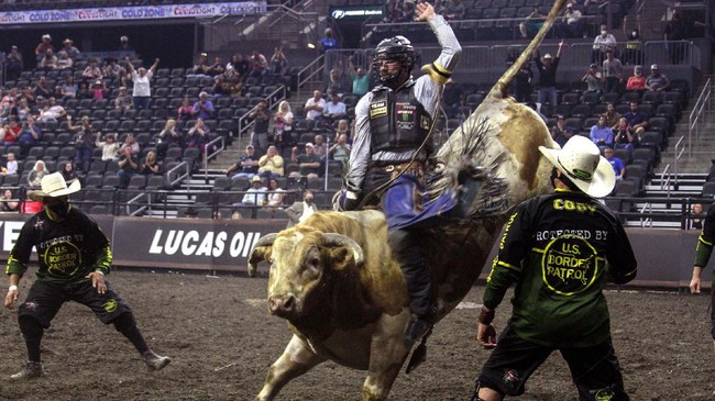 Lane Lasley rides a bull in the Monster Energy Team Challenge in Sioux Falls, S.D., Friday.July 10, 2020, as Professional Bull Riders welcomed just over 1,000 fans into the arena that usually holds 9,000. (AP Photo/Stephen Groves)