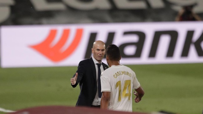 Real Madrid's head coach Zinedine Zidane, talks to his player Casemiro after he was substituted, during the Spanish La Liga soccer match between Real Madrid and Deportivo Alaves at the Alfredo di Stefano stadium in Madrid, Spain, Friday, July 10, 2020. (AP Photo/Bernat Armangue)