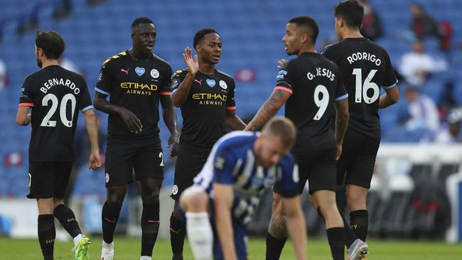 Manchester City's Raheem Sterling, center, celebrates after scoring his side's opening goal during the English Premier League soccer match between Brighton and Manchester City at the Falmer stadium in Brighton, England, Saturday, July 11, 2020. (Julian Finney/Pool via AP)