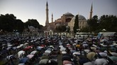 Muslims offer their evening prayers outside the Byzantine-era Hagia Sophia, one of Istanbul's main tourist attractions in the historic Sultanahmet district of Istanbul, following Turkey's Council of State's decision, Friday, July 10, 2020. Turkey's highest administrative court issued a ruling Friday that paves the way for the government to convert Hagia Sophia - a former cathedral-turned-mosque that now serves as a museum - back into a Muslim house of worship. The Council of State threw its weight behind a petition brought by a religious group and annulled a 1934 cabinet decision that changed the 6th century building into a museum. (AP Photo/Emrah Gurel)