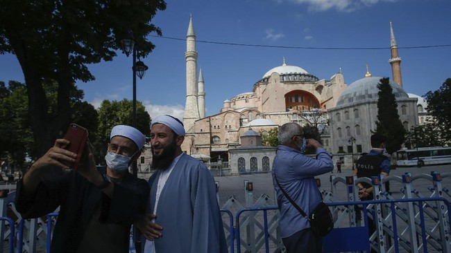 People use their mobile to take a selfie picture outside the now closed Byzantine-era Hagia Sophia, one of Istanbul's main tourist attractions in the historic Sultanahmet district of Istanbul, Saturday, July 11, 2020. Turkey's President Recep Tayyip Erdogan formally reconverted Hagia Sophia into a mosque and declared it open for Muslim worship, hours after a high court annulled a 1934 decision that had made the religious landmark a museum.The decision sparked deep dismay among Orthodox Christians. Originally a cathedral, Hagia Sophia was turned into a mosque after Istanbul's conquest by the Ottoman Empire but had been a museum for the last 86 years, drawing millions of tourists annually. (AP Photo/Emrah Gurel)