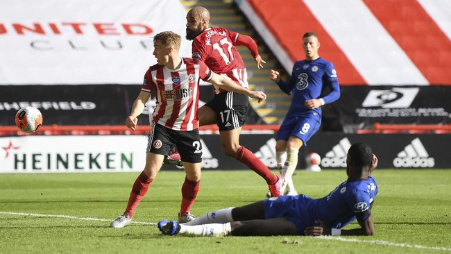 Sheffield United's David McGoldrick, second left, scores his side's third goal during the English Premier League soccer match between Sheffield United and Chelsea at Bramall Lane in Sheffield, England, Saturday, July 11, 2020. (Shaun Botterill/Pool via AP)