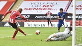 Sheffield United's David McGoldrick, left, scores his side's opening goal during the English Premier League soccer match between Sheffield United and Chelsea at Bramall Lane in Sheffield, England, Saturday, July 11, 2020. (Peter Powell/Pool via AP)