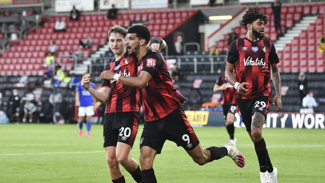 Bournemouth's Dominic Solanke, centre, is congratulated by teammate David Brooks, left, after scoring his team's second goal during the English Premier League soccer match between Bournemouth and Leicester City at Vitality Stadium in Bournemouth, England, Sunday, July 12, 2020. (AP Photo/Glynn Kirk,Pool)