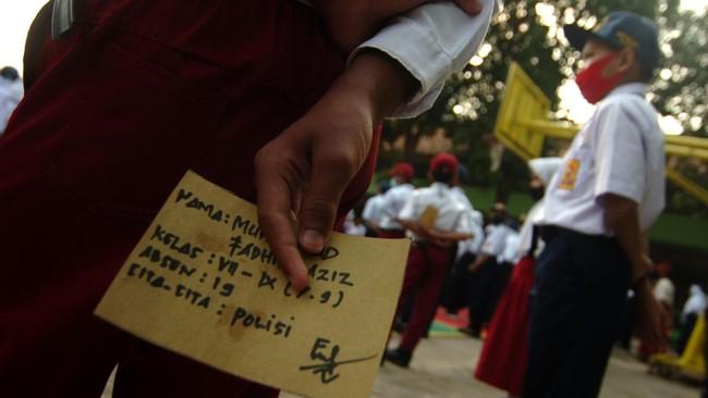 Sejumlah siswa-siswi baru mengikuti upacara di SMPN 1 Slawi, Kabupaten Tegal, Jawa Tengah, Senin (13/7/2020). Pihak sekolah setempat mengharapkan siswa baru menerapkan protokol kesehatan COVID-19 selama mengikuti kegiatan Masa Pengenalan Lingkungan Sekolah (MPLS) selama tiga hari karena Kabupaten Tegal masih di zona merah. ANTARA FOTO/Oky Lukmansyah/wsj.