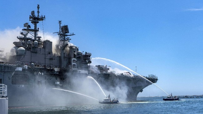 """In a photo provided by the U.S. Navy, Port of San Diego Harbor Police boats fight a fire aboard the USS Bonhomme Richard at Naval Base San Diego on Sunday, July 12, 2020. Twenty-one people suffered minor injuries in an explosion and fire on the ship, military officials said. The blaze was reported shortly before 9 a.m., said Mike Raney, a spokesman for Naval Surface Force, U.S. Pacific Fleet. Seventeen sailors and four civilians were hospitalized with """"non-life threatening injuries,"""" Raney said in a brief statement. (Petty Officer 3rd Class Christina Ross/U.S. Navy via AP)"""