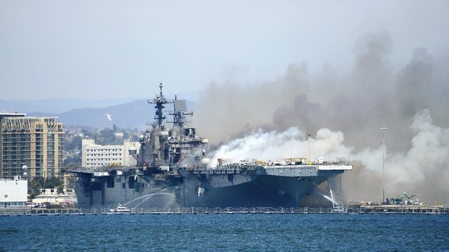 """In a photo provided by the U.S. Navy, Port of San Diego Harbor Police boats fight a fire aboard the USS Bonhomme Richard at Naval Base San Diego, Sunday, July 12, 2020. Twenty-one people suffered minor injuries in an explosion and fire Sunday on board a ship, military officials said. The blaze was reported shortly before 9 a.m., said Mike Raney, a spokesman for Naval Surface Force, U.S. Pacific Fleet. Seventeen sailors and four civilians were hospitalized with """"non-life threatening injuries,"""" Raney said in a brief statement. (Lt. John J. Mike/U.S. Navy via AP)"""