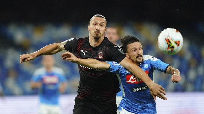 AC Milan's Zlatan Ibrahimovic, left, and Napoli's Mario Rui vie for the ball during a Serie A soccer match at San Paolo Stadium in Naples, Italy, Sunday, July 12, 2020. ISpada/LaPresse via AP)