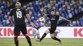 Napoli's Dries Mertens, rear, kicks the ball past AC Milan's Alessio Romagnoli, right, during a Serie A soccer match at San Paolo Stadium in Naples, Italy, Sunday, July 12, 2020. (Cafaro/LaPresse via AP)