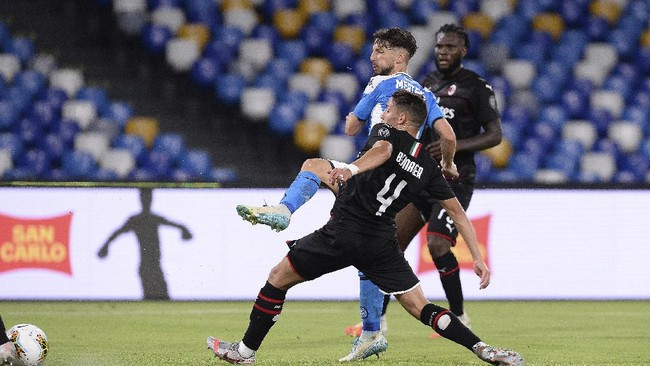 Napoli's Dries Mertens (SSC Napoli) scores as AC Milan's Ismaël Bennacer (4) defends during a Serie A soccer match at San Paolo Stadium in Naples, Italy, Sunday, July 12, 2020. (Cafaro/LaPresse via AP)